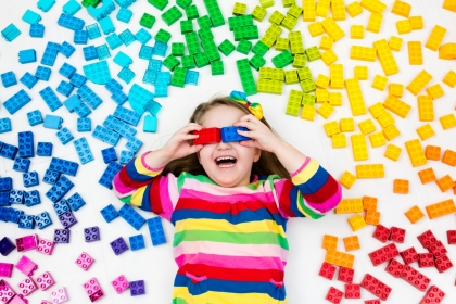 Funny little girl playing with colorful rainbow plastic blocks. Kids play, create and learn colors. Educational toys for creative children. Preschooler building block toys. Kid playing on the floor.
